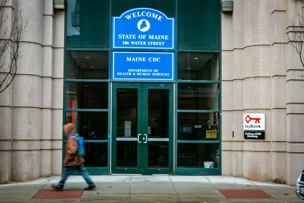 A man walks by the Maine Center for Disease Control on water Street in Augusta on Thursday.